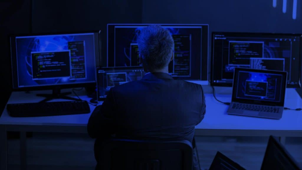 man at desk with computers